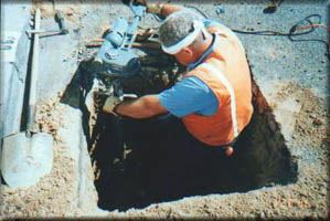 Worker Emerging from the Ground to Grab a Pipe